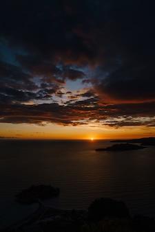 Feuriger goldener sonnenuntergang in montenegro über dem meer in der nähe von sveti stefan und der insel st nicholas on