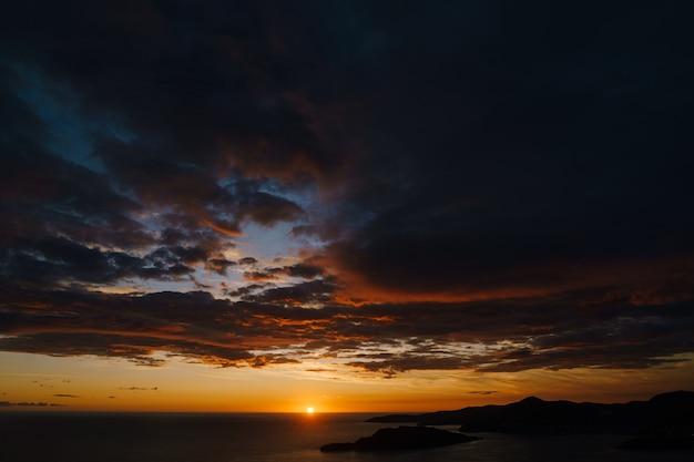 Feuriger goldener sonnenuntergang in montenegro über dem meer nahe sveti stefan und der insel von st nicholas auf