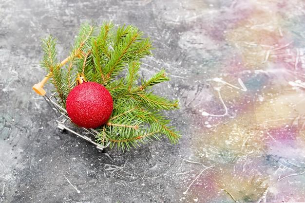 Fichtengrüner zweig und rot glänzender weihnachtsbaum-spielzeugball in einem miniatur-einkaufswagen auf schwarzem hintergrund, kopierraum