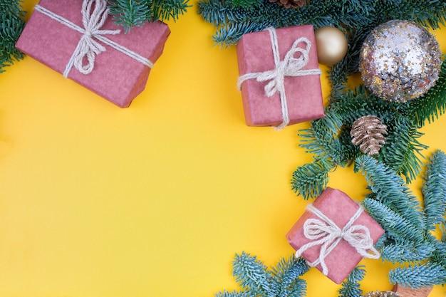 Fichtenzweig, zapfen und vintage-spielzeugdekoration zu weihnachten oder neujahr auf gelbem hintergrund.