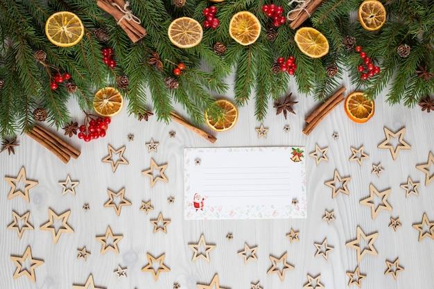 Fichtenzweige, dekor, beeren, orangenscheiben, zimt und eine postkarte, ein brief an den weihnachtsmann