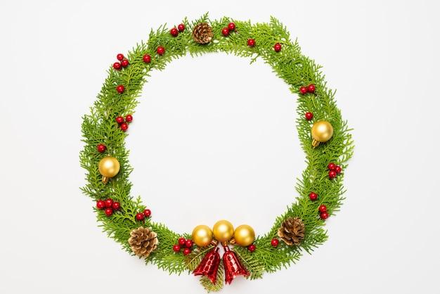 Fichtenzweige, kiefernkegel, rote beeren und goldener ball auf weißem hintergrund für weihnachten