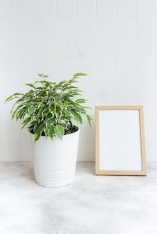 Ficus benjamin und mock-up-posterrahmen auf dem tisch
