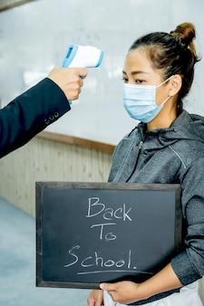 Fieberkontrolle der jungen frau durch den professor, bevor sie zum unterricht geht. zurück zum schulkonzept.