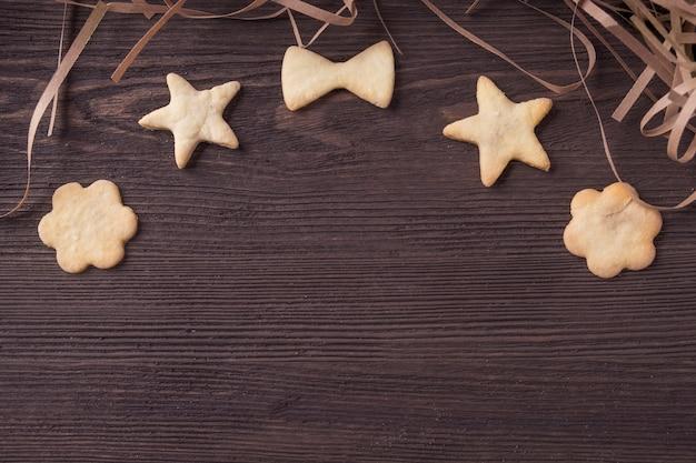 Figürliche hausgemachte shortbread-kekse auf hölzernem hintergrund mit platz für text. draufsicht. copyspace
