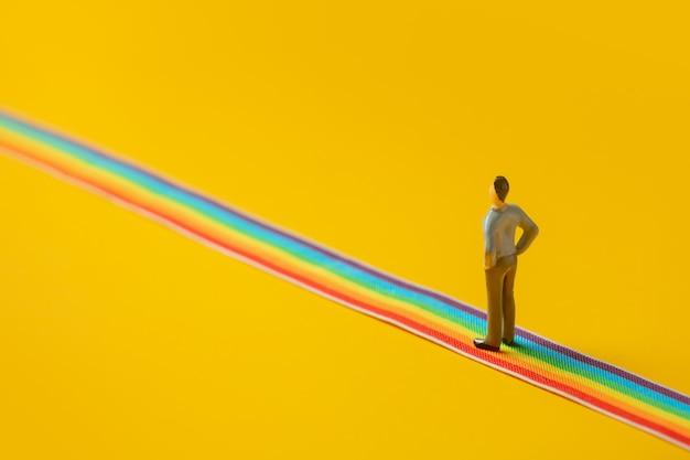 Figur des erwachsenen mannes auf regenbogen-lgbt-streifen auf gelbem hintergrund