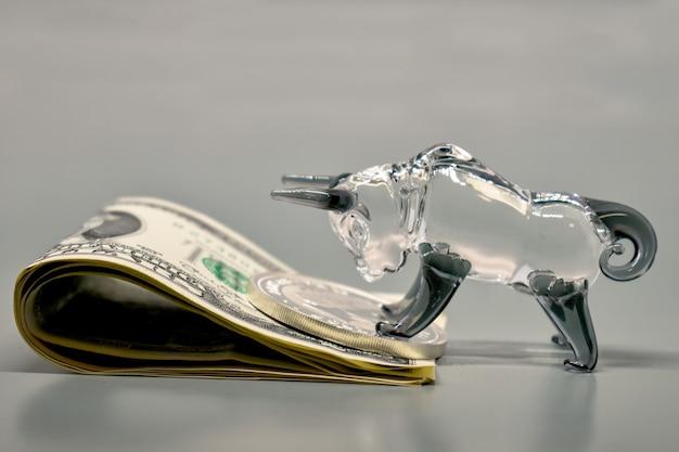 Figur des stiers mit banknoten auf grauem hintergrund. geschäftskonzept, börse, finanzen.