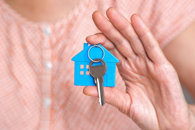 Figur eines blauen minihauses mit den schlüsseln in der hand einer person