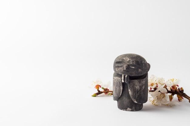 Figur eines buddhistischen mönchs und einer niederlassung eines kirschbaums mit blumen. konzept des frühlings und des chinesischen neuen jahres.
