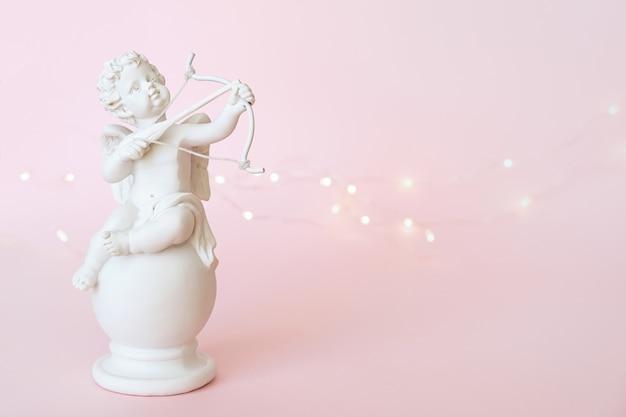Figur eines engels amors mit einem bogen auf einem rosa hintergrund. valentinstag.