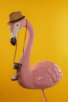 Figur eines rosa flamingotouristen in einem strohhut, der eine kamera hält