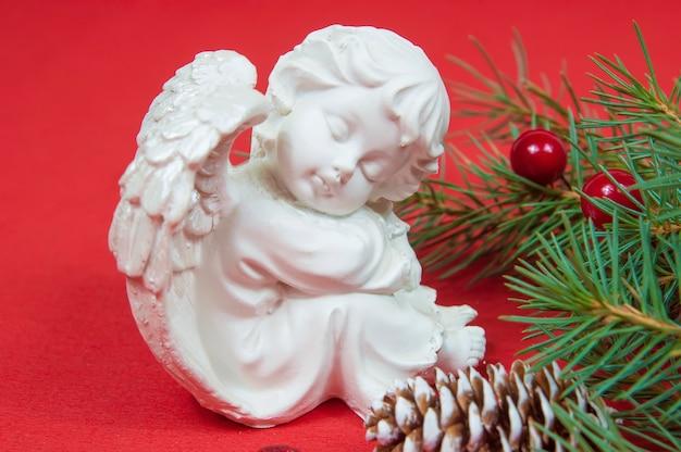 Figur eines weihnachtsengels, der nahe den zweigen eines weihnachtsbaumes mit zapfen auf einem roten hintergrund sitzt