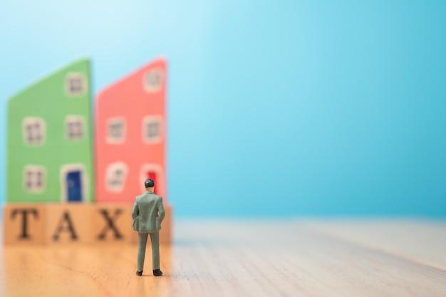 Figur geschäftsmann, der vor einem holzhaus auf steuer steht. das konzept der finanzierung und investition in wohnimmobilien und steuerzahlung.
