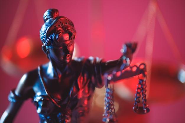 Figur von lady justice im notariat nahaufnahme in neon. symbol für gerechtigkeit und gesetz.