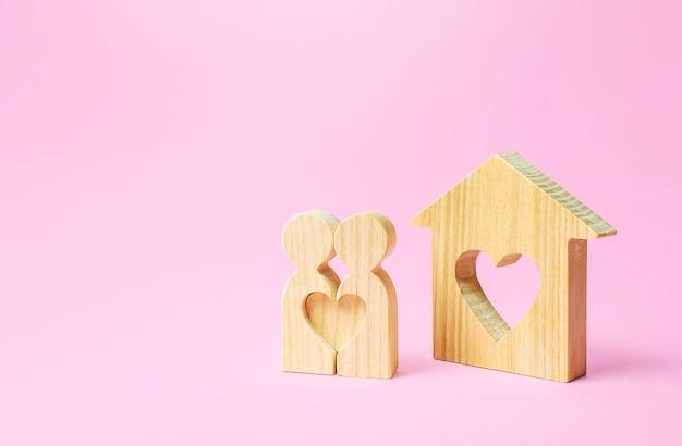 Figuren eines liebespaares stehen in der nähe des hauses mit herz. erschwingliche billige unterkunft für junge paare