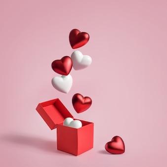 Figuren in form eines herzens fliegen aus einer offenen schachtel auf einer rosa oberfläche mit kopierraum.