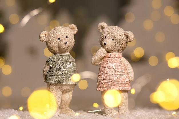 Figuren von niedlichen teddybären eines jungen und eines mädchens in pullovern mit hirschen