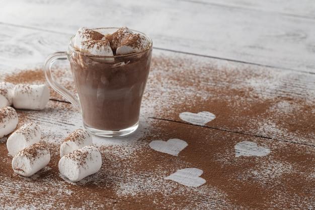 Figurenzeichnungen in form eines herzens auf dem kakaopulver verstreut