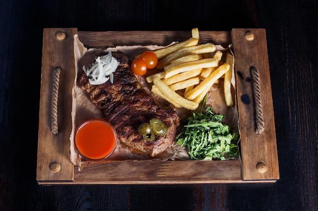 Filetsteak mit pommes frites auf einem holztablett, schöne portion, dunkler hintergrund.