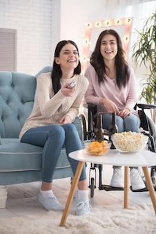 Film abspielen. glückliche schwester und behinderte frau, die film auswählt und lacht Premium Fotos