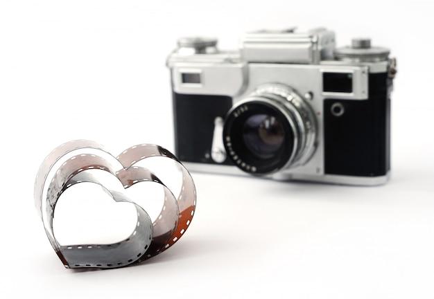 Film in form von herzen auf dem hintergrund der retro-filmkamera