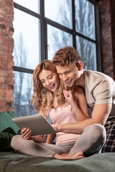 Film zusammen. blonde schöne glückliche freundin, die mit ihrem gutaussehenden mann einen film auf dem tablet sieht