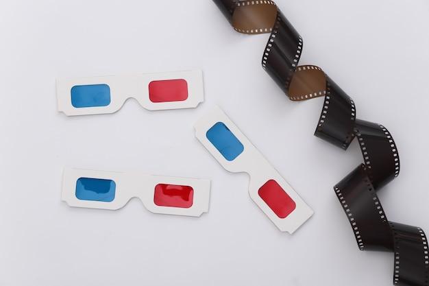 Filmband und 3d-brille auf weißem hintergrund. ãinema, unterhaltungsindustrie. ansicht von oben