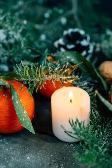 Filmblickbild weihnachtszusammensetzung mit tangerinen, kiefernkegeln, walnüssen und kerzen auf hölzernem hintergrund.