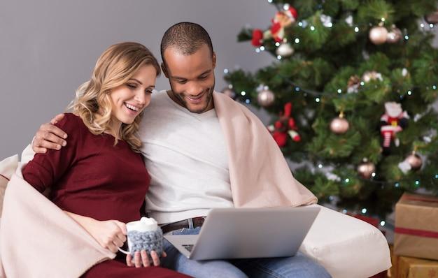 Filme gucken. angenehmes glückliches nettes paar, das zusammen auf dem sofa sitzt und auf den laptopbildschirm schaut, während man zusammen einen film sieht