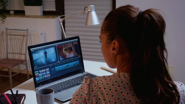 Filmemacher, der einen film mit moderner software für die postproduktion bearbeitet. videofilmer, der an einer audiofilmmontage auf einem professionellen laptop arbeitet, der um mitternacht auf dem schreibtisch in einer modernen küche sitzt
