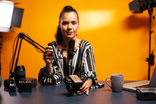 Filmemacher, der einen flüssigkeitskopf hält und während des podcasts im heimstudio darüber spricht