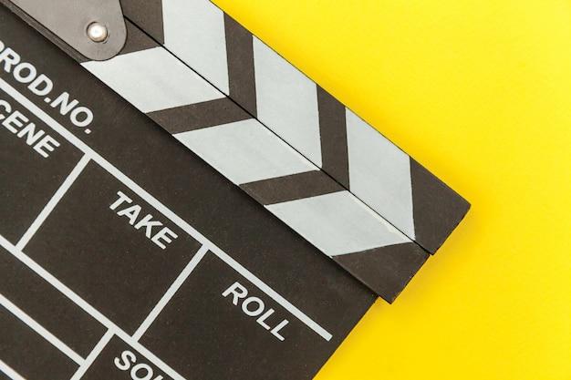 Filmemacherberuf. klassischer regisseur leerer film, der filmklappe oder filmschiefer auf gelb isoliert macht. konzept der videoproduktionsfilmkinoindustrie. flat lay draufsicht kopierraum modell.