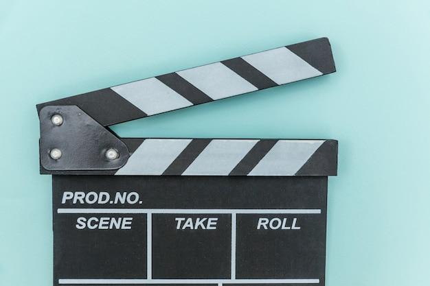 Filmemacherberuf. klassischer regisseur leerer film, der filmklappe oder filmschiefer lokalisiert auf blauer wand macht. konzept der videoproduktionsfilmkinoindustrie. kopierraum für flache draufsicht.