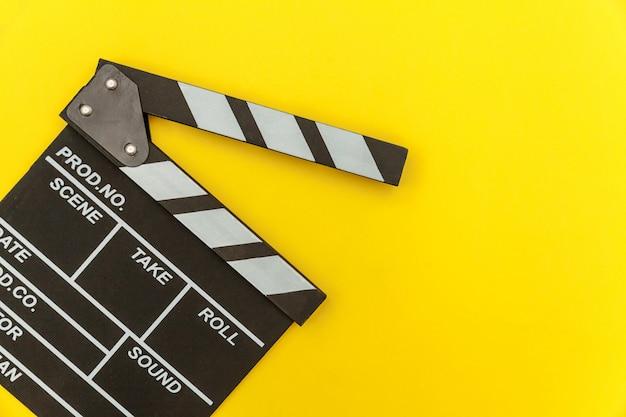 Filmemacherberuf. leerer film des klassischen regisseurs, der klappe oder filmschiefer lokalisiert auf gelbem hintergrund macht. konzept der videoproduktionsfilmkinoindustrie. flat lay draufsicht kopierraum modell.