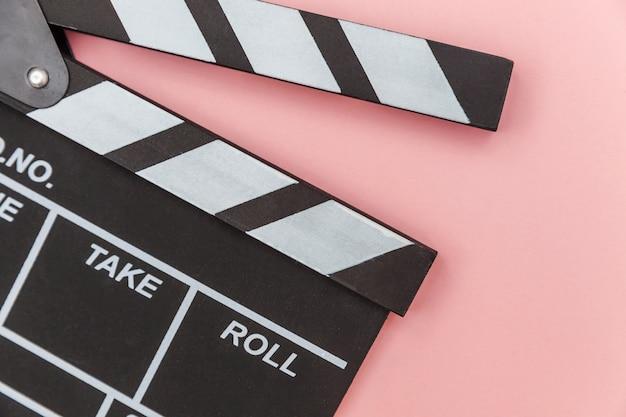 Filmemacherberuf. leerer film des klassischen regisseurs, der klappe oder filmschiefer lokalisiert auf rosa wand macht. konzept der videoproduktionsfilmkinoindustrie. kopierraum für flache draufsicht.