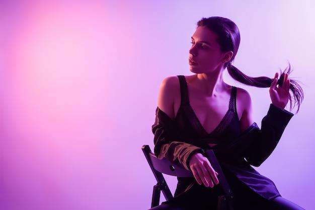 Filmisches nachtporträt der frau im neon. schöne junge frau in stilvolle kleidung, die auf stuhl in den bunten lichtern aufwirft.