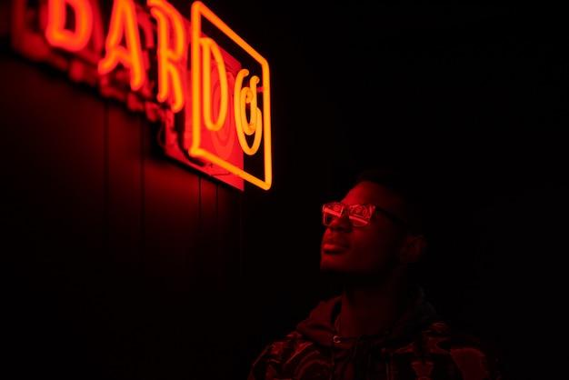 Filmisches porträt des gutaussehenden mannes mit sonnenbrille mit kühlen neonlichtern