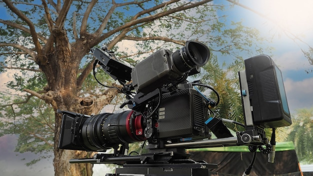Filmkamera. hinter der videokamera, die zum aufnehmen von filmwerbung oder filmen im freien dient. 4k-digitalkamera im 35-mm-filmstil und stativ-dolly-kran für die videoproduktion. filmindustrie.