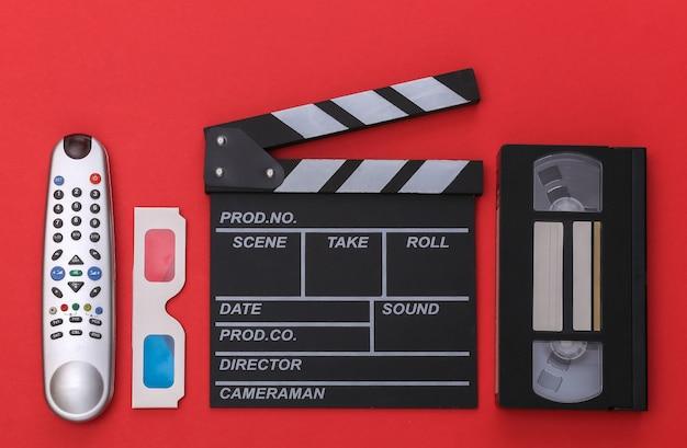 Filmklappe, 3d-brille, videokassette und tv-fernbedienung auf rotem hintergrund. ansicht von oben