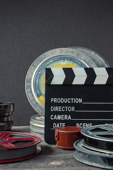 Filmklappe, eine schachtel film und objektiv