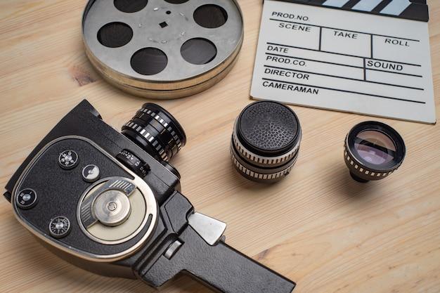 Filmklappe, filmrolle und kamera auf holztisch, ansicht von oben