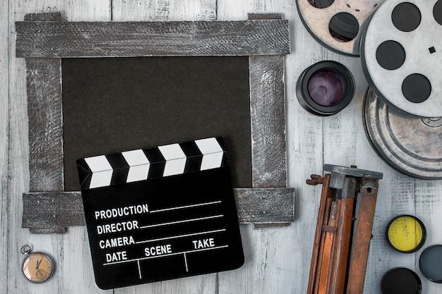 Filmklappe, filmrollen und ein stativ