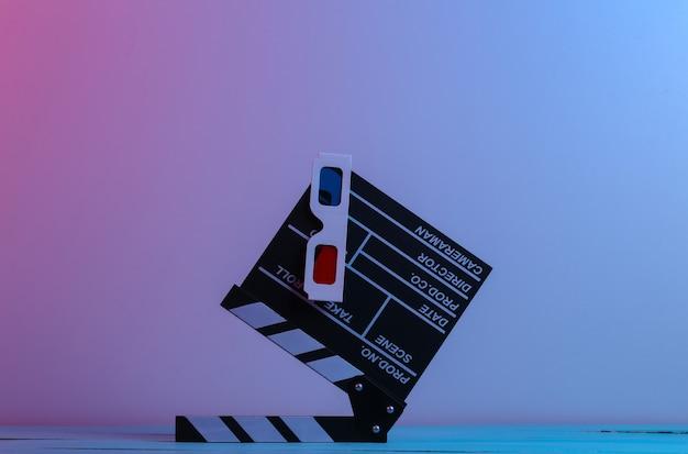 Filmklappe mit 3d-brille in rot-blauem neonlicht. unterhaltungsindustrie