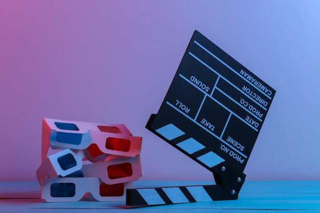 Filmklappe und 3d-brille in rot-blauem neonlicht. unterhaltungsindustrie