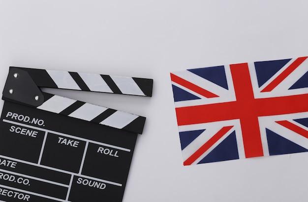 Filmklappe und britische flagge auf weißem hintergrund. filmemachen, filmproduktion, unterhaltungsindustrie. ansicht von oben
