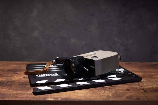 Filmklappe und film retro-kamera am tisch hintergrundtextur