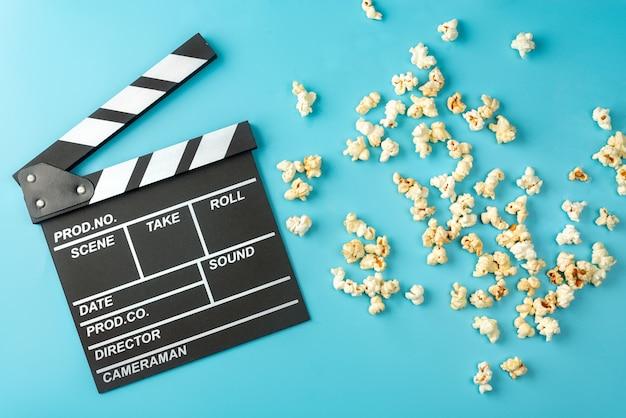 Filmklappe und popcorn auf blau