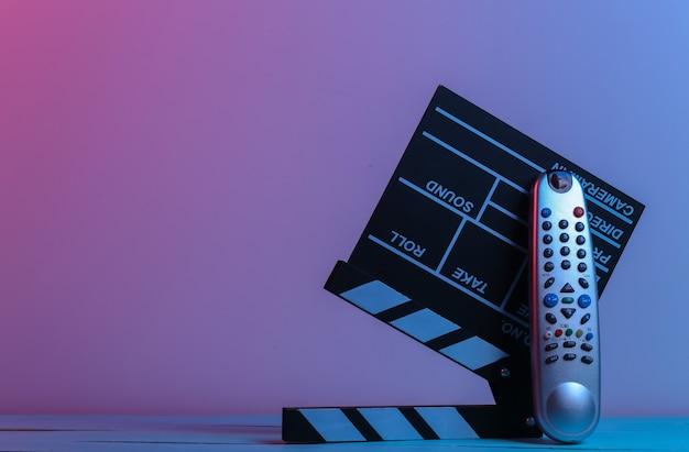 Filmklappe und tv-fernbedienung in rot-blauem neonlicht. unterhaltungsindustrie