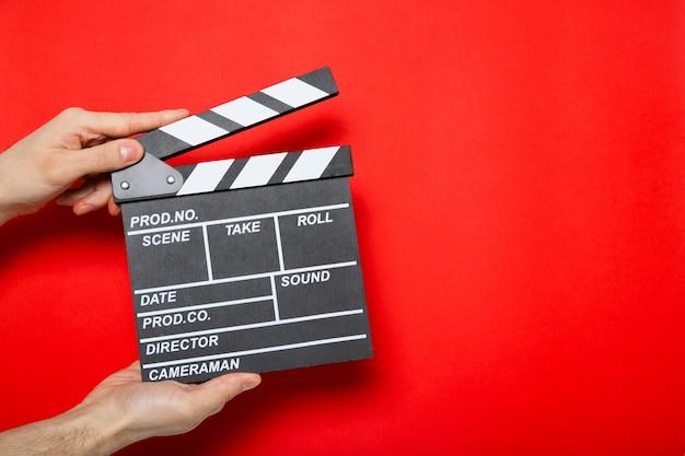 Filmklöppel in den händen eines mannes an einer roten wand mit platz für text