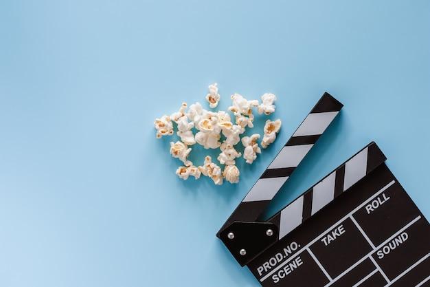 Filmscharnierventilbrett mit popcorn auf blauem hintergrund für unterhaltung